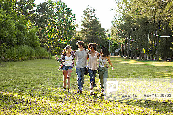 Happy young friends walking together in park