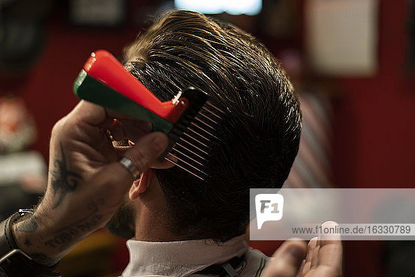 Hairdresser styling man's hair in salon