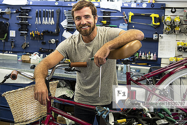 Mechanic leaning on bicycle