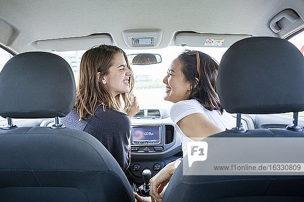 Smiling young female friends enjoying a road trip