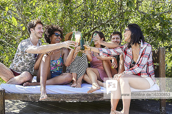 Young friends enjoying drinks at poolside