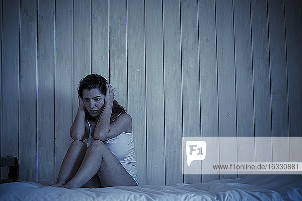 Sad young woman sitting on bed