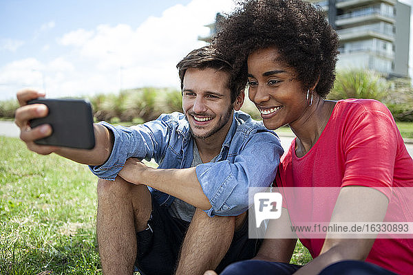 Young couple taking selfie on smartphone in park
