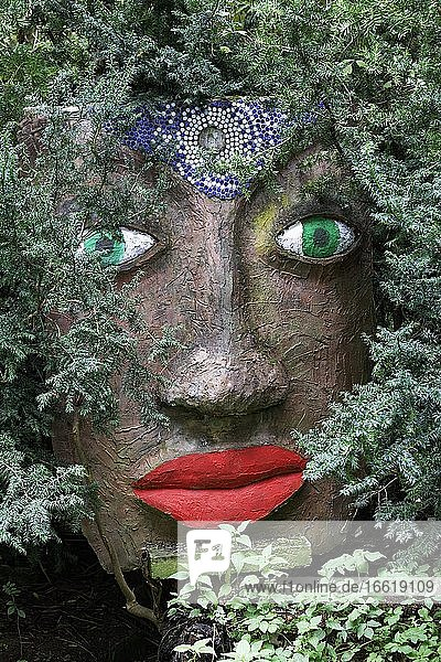Magical woman face with red lips and green eyes looks through branches  sculpture  sculpture garden by the artist Jochen Bach  Plinzmühle  Plinz  Großkröbitz  Milda  Thuringia  Germany  Europe
