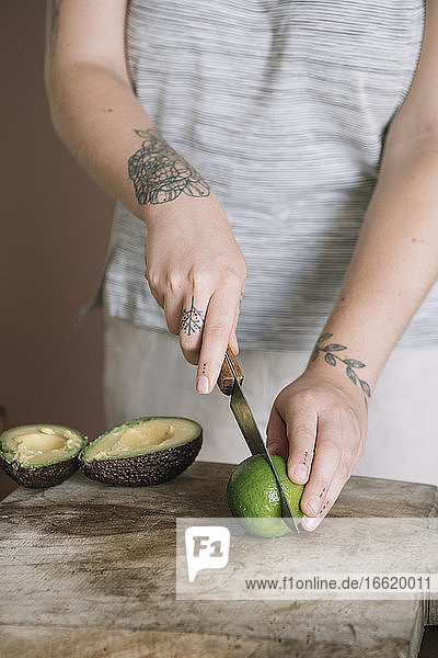 Young woman cutting lime while standing at kitchen
