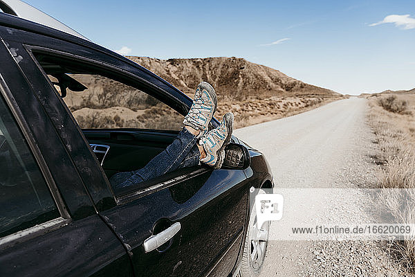 Spain  Navarre  Young woman sticking legs out of car window over over dirt road in Bardenas Reales