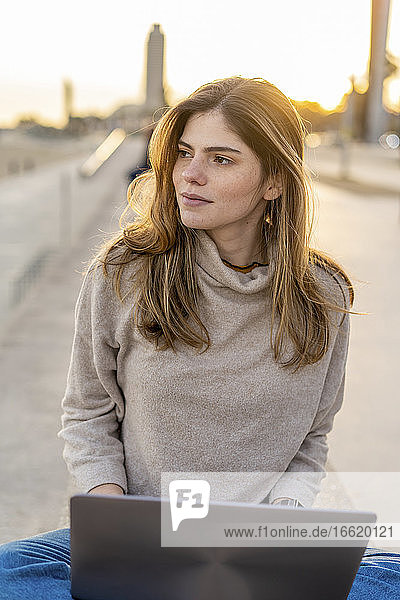 Beautiful young woman looking away while sitting with laptop at promenade during sunset