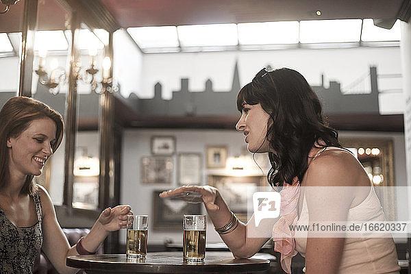 Weibliche Freunde unterhalten sich bei einem Bier in einer Kneipe