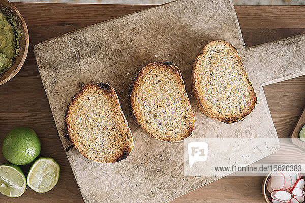 Homemade baked bread kept on cutting board at kitchen