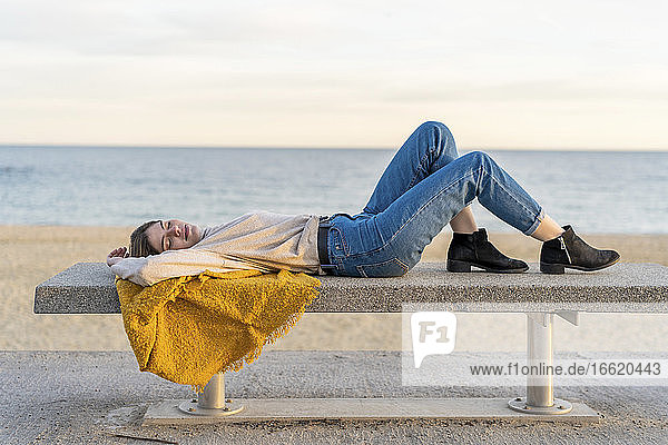 Young woman lying on bench at beach promenade during sunset