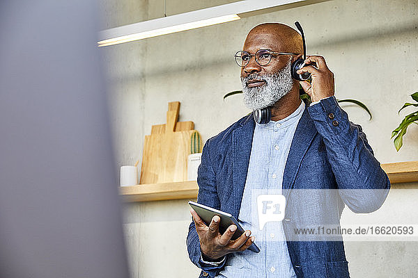 Man with headphone and digital tablet looking away while standing at home