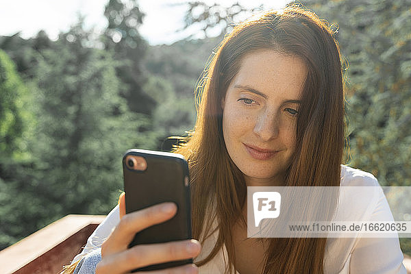Young woman taking selfie while standing in balcony on sunny day