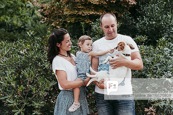 Family standing with pet dog in public park