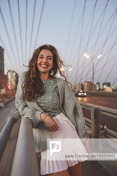 Smiling woman standing on bridge against sky in city during sunset