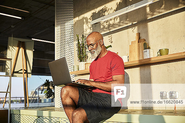 Mature man concentrating on work while using laptop at home