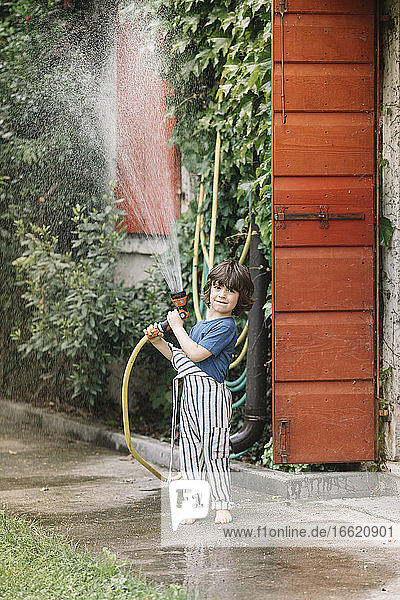 Boy playing with garden hose while standing at backyard