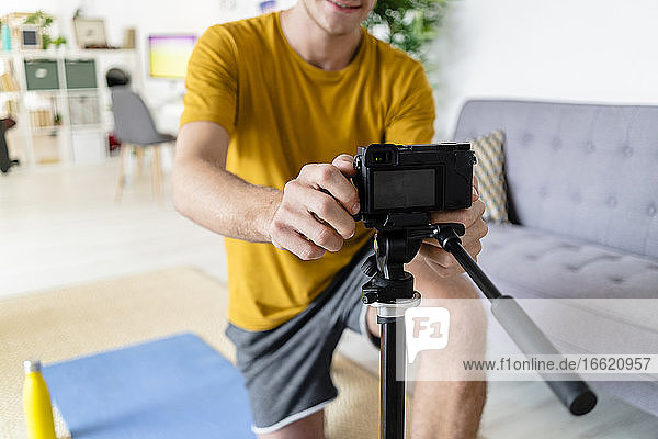 Young man adjusting video camera while sitting at home