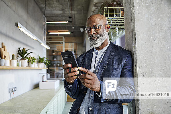 Mature man text messaging on smart phone while standing at home