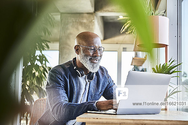 Smiling mature businessman working from home on laptop