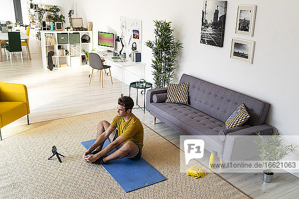 Man watching mobile phone while exercising at home