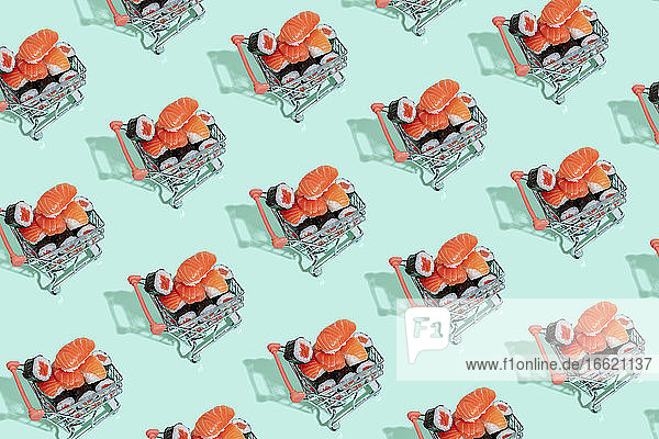 Multiple image of fresh sushi in shopping carts on mint green background