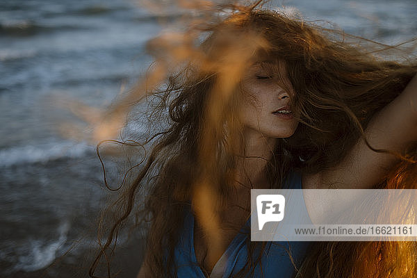 Young woman face covered with hair while dancing at beach