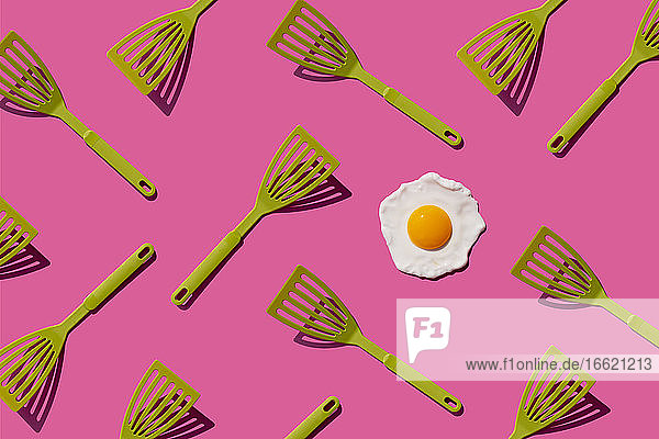Pattern of green spatulas with single fried egg