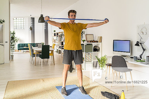 Man exercising with stretchable rubber while standing at home