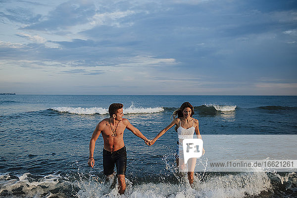 Couple holding hand while walking in water at beach