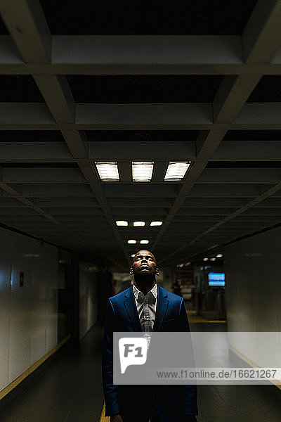 African businessman with eyes closed standing under illuminated light in subway