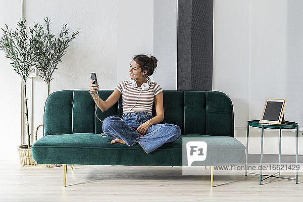 Smiling female design professional taking selfie while sitting on sofa during break in office