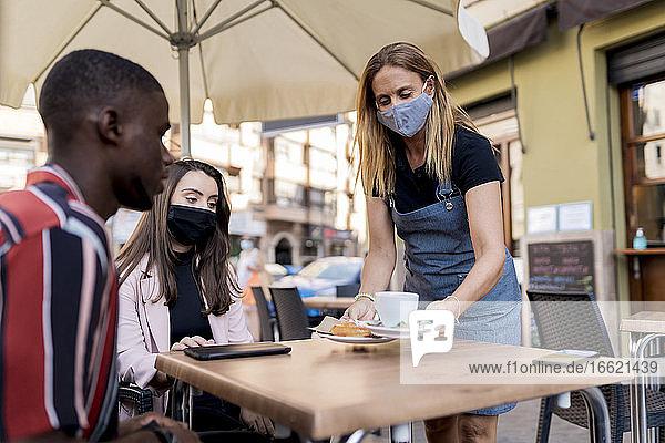 Kellnerin mit Gesichtsmaske bedient junges Paar in einem Café während des COVID-19-Ausbruchs