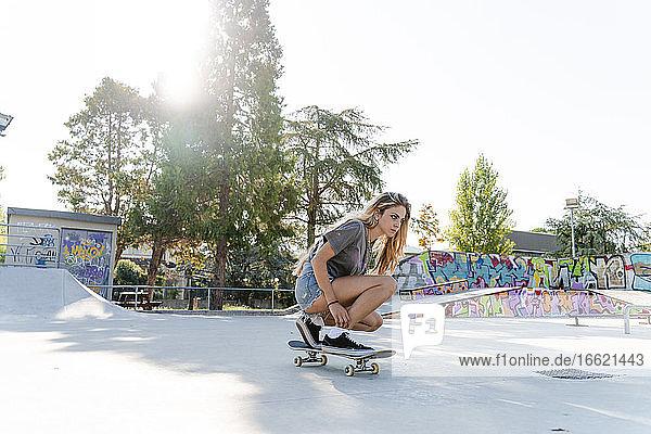 Blond woman skateboarding at park against sky on sunny day