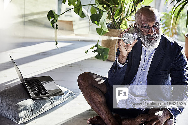 Man listening from tin can phone while sitting at home