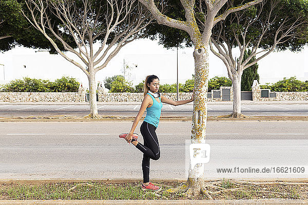 Young Latin woman stretching leg while leaning on tree trunk by street