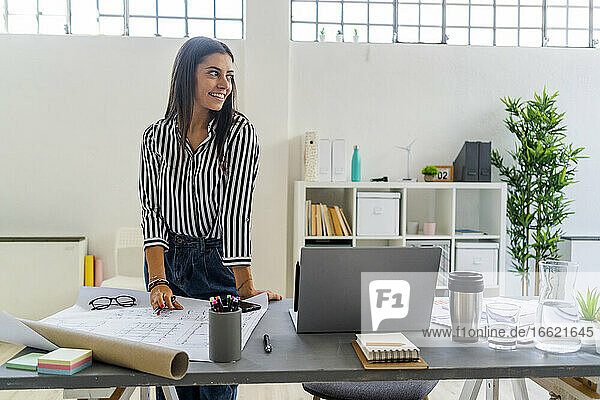 Smiling businesswoman looking away while standing at desk in creative office