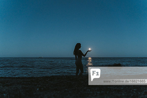 Optical illusion of silhouette woman holding moon over sea against clear sky at night