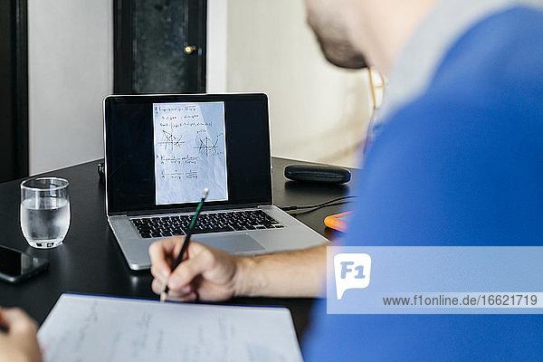 Male university student doing mathematics homework through laptop at home
