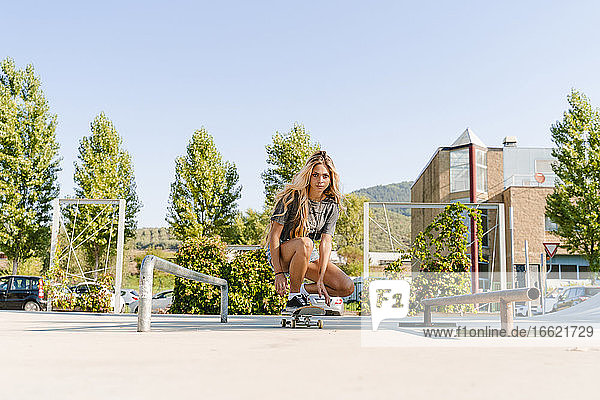 Confident young woman skateboarding at park against clear sky on sunny day
