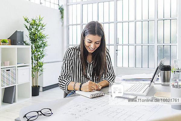 Smiling young female architect writing in diary while sitting at desk in office