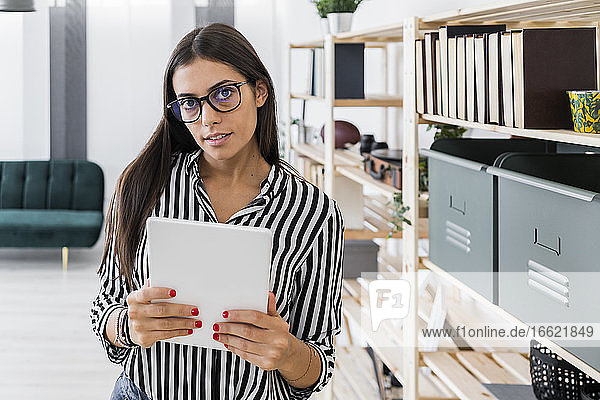 Confident beautiful young female architect holding digital tablet while standing by rack at creative office