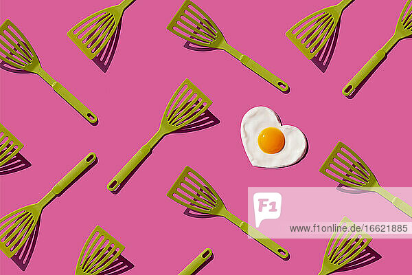 Pattern of green spatulas with single heart shaped fried egg