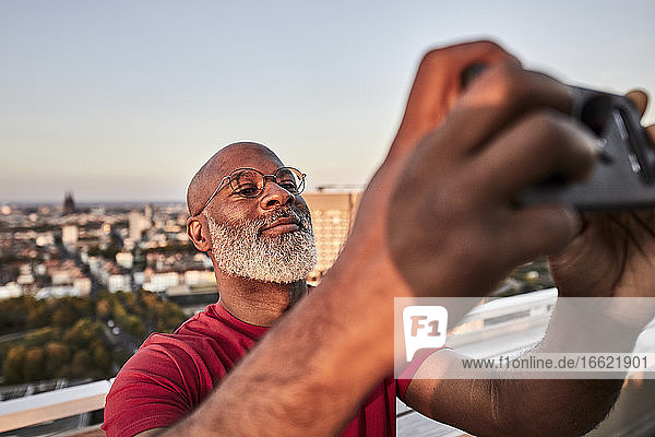 Bearded mature man using smart phone for photographing sunset from rooftop in city