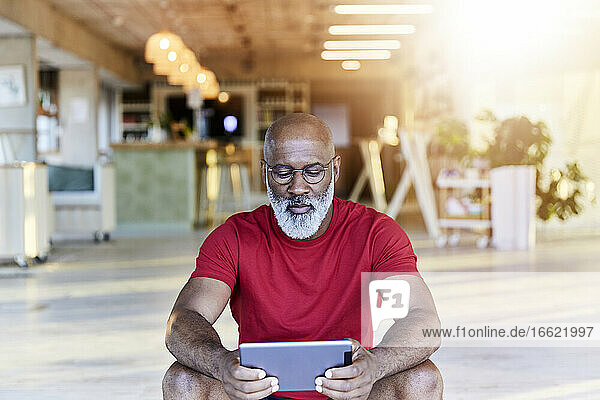 Mature man in red t-shirt using digital tablet while sitting at rooftop