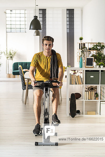 Young man cycling on exercise equipment at home