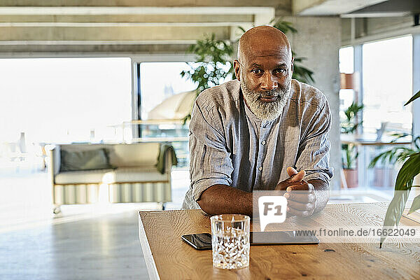 Confident bald man with hands clasped leaning on table at rooftop