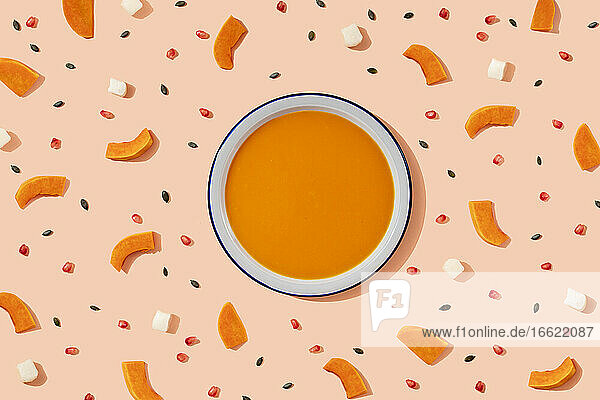 Studio shot of bowl of pumpkin soup surrounded by pumpkin seeds  pomegranate seeds and pieces of cheese and pumpkin