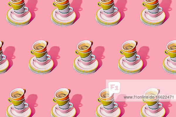 Pattern of stack of plates and coffee cups against pink background