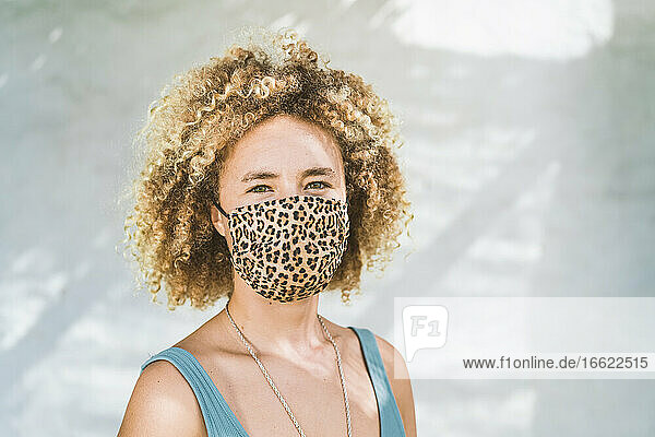 Blond woman wearing protective face mask standing against wall