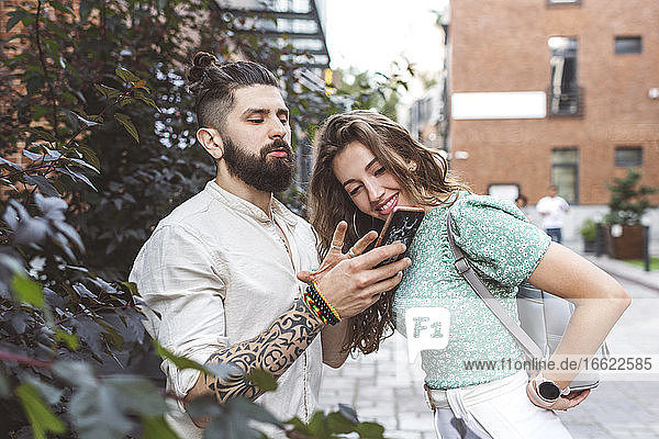Boyfriend gesturing while showing smart phone to girlfriend on footpath in city